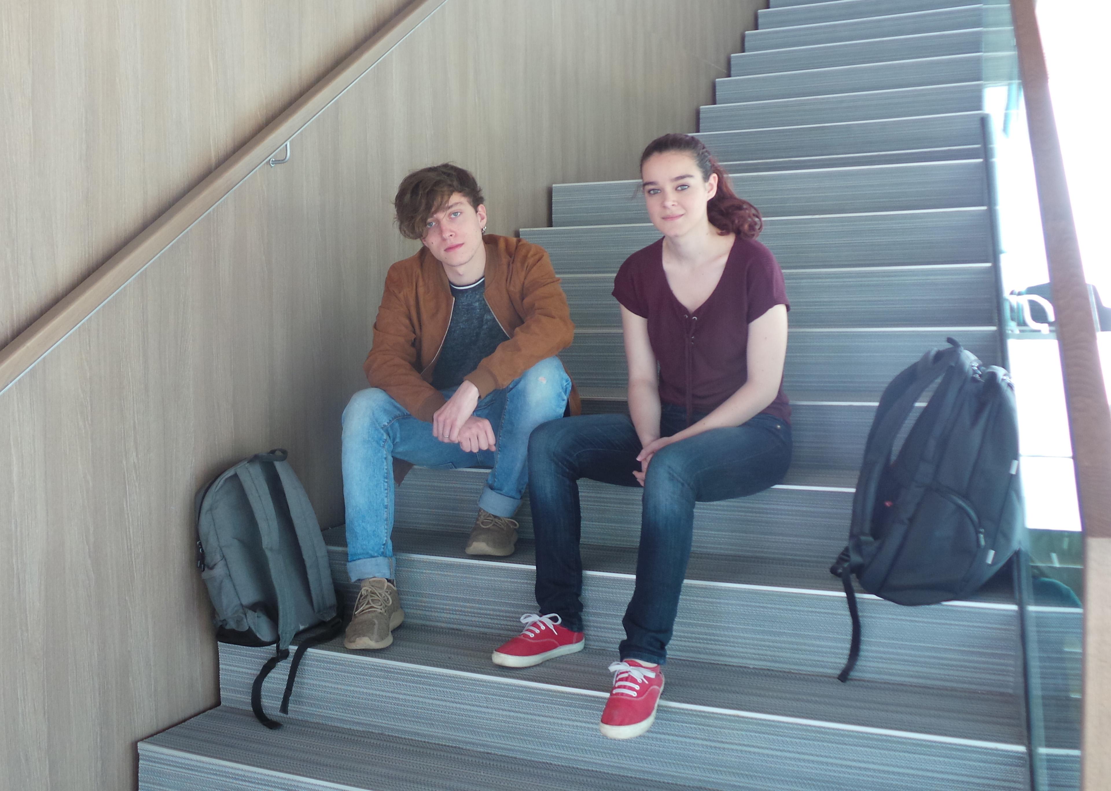 Javier Fajarnés y Mar Zamorano, beneficiarios de la Beca a la Excelencia, en las escaleras del hall del Edificio Estudiantes