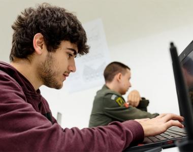 Alumno con ordenador en un aula