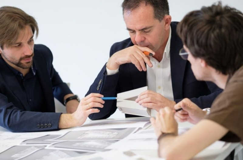 Profesor de arquitectura trabajandi con dos alumnos de la escuela de arquitectura y tecnología