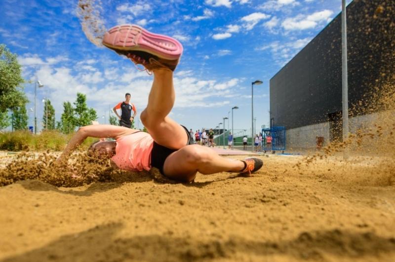 Alumno de CAFD realizando un salto de longitud en el campus deportivo de la Universidad San Jorge